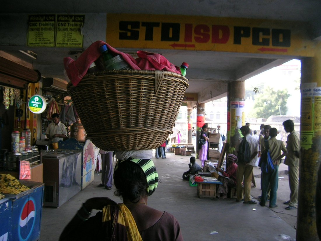 woman carrying her wares on her head in a bus station in the south of India. She starts the day knowing that the competition is fierce...
