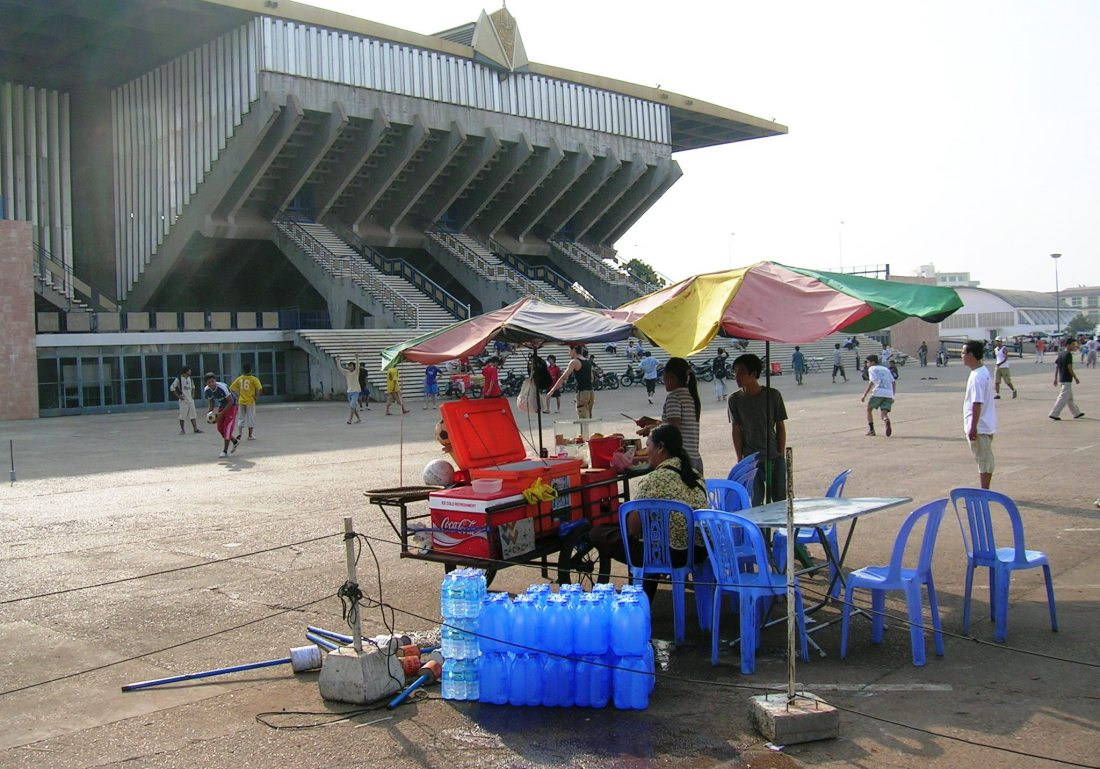 Serving cool drinks outside the beautiful sports stadium built during the 1970's under Sihanouk